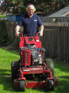 Man with lawn mower cutting grass