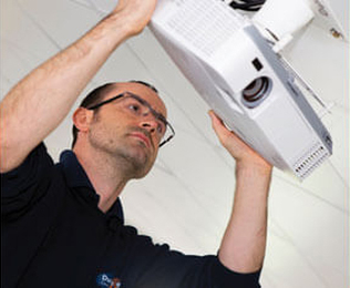 Man inspecting a projector