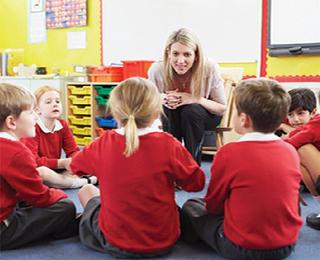 School children sat on floor listening to teacher
