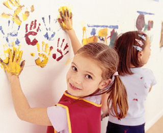 Child putting hand prints on wall with paint