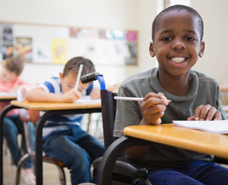 School boy taking exam smiling at camera