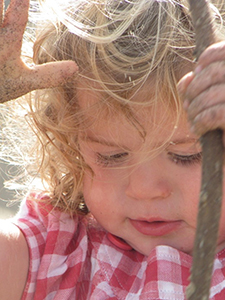 Child playing in sand with a stick