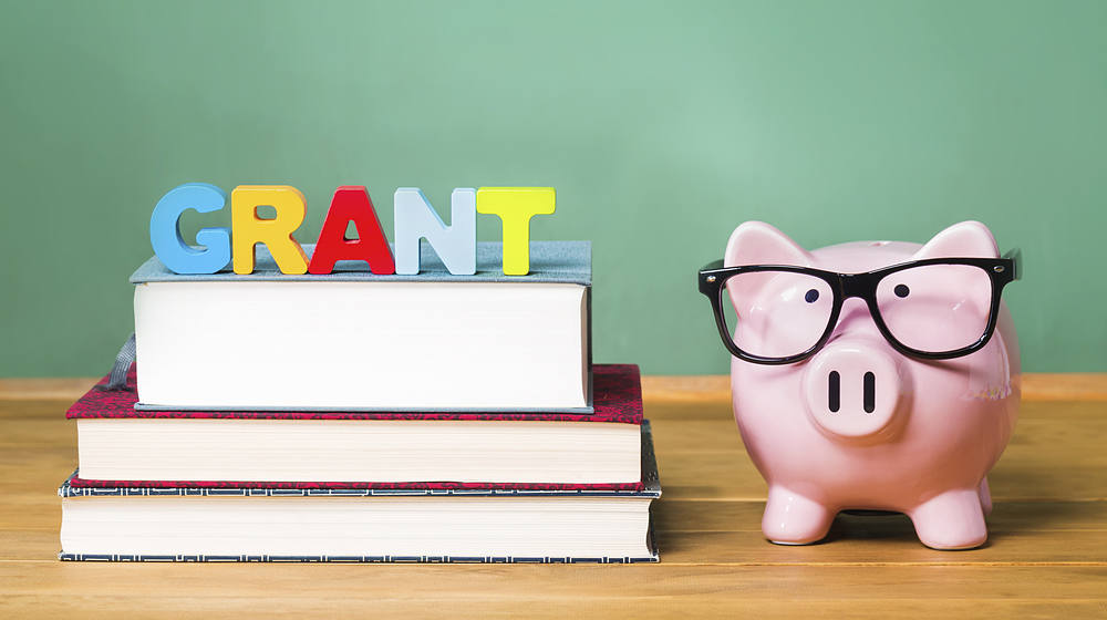 The word Grant set atop books with a piggy bank wearing glasses beside them