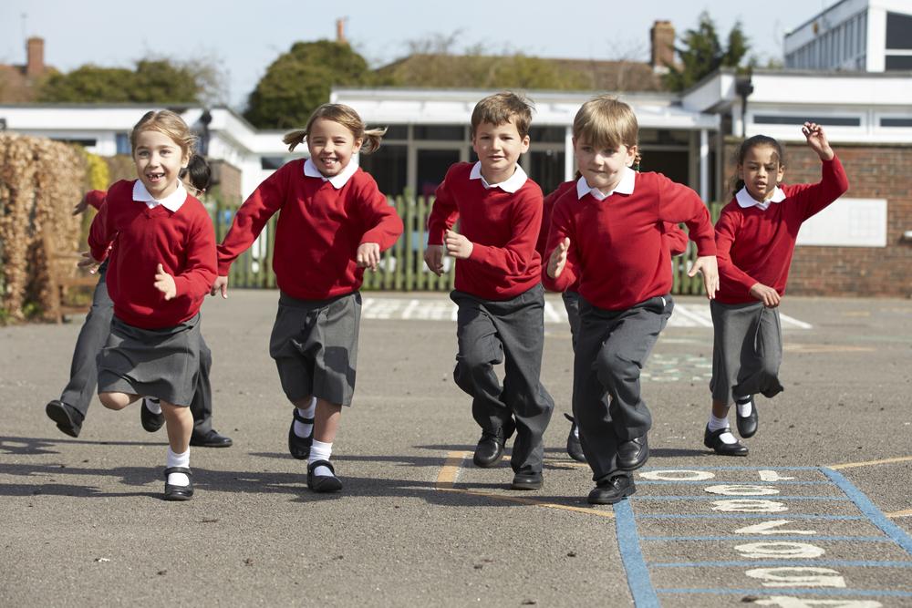 School children running in playground, smiling